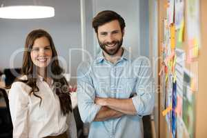 Portrait of smiling business colleagues standing by soft board