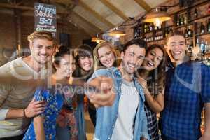 Happy friends taking selfie in pub