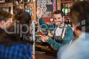 Smiling bartender pouring beer in glass for customers