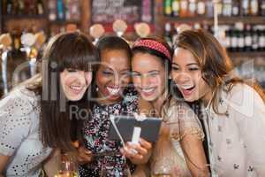 Cheerful female friends taking selfie in pub