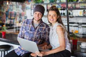 Portrait of friends using laptop in restaurant