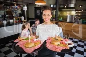 Waitress serving burger while customers sitting in restaurant