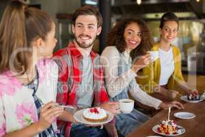 Happy friends having dessert in cafe