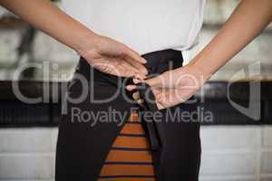 Close up of waitress tying apron