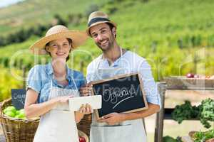 Portrait of happy couple holding chalkboard while using digital tablet