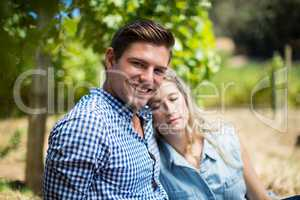Woman sleeping on man shoulder at vineyard