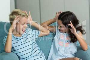 Boy and girl sitting on sofa teasing each other in living room