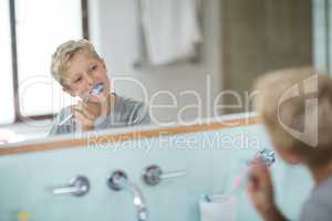 Boy brushing his teeth in bathroom