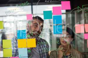 Male and female executives discussing over sticky notes