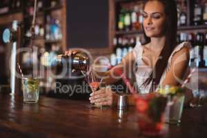 Female bartender pouring cocktail drink in the glass