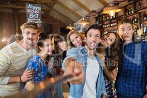 Cheerful friends taking selfie in pub