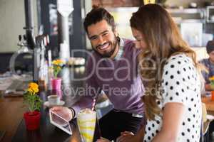 Portrait of cheerful man holding digital tablet while sitting with female friend