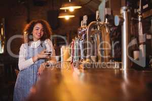 Portrait of young woman having wine at counter