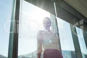 Businesswoman standing by brightly lit window in office