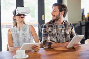 Man looking at friend wearing virtual reality glasses