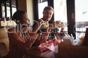 Happy couple eating burger