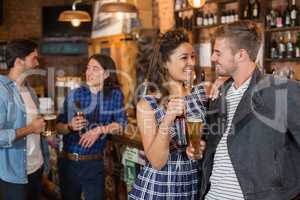 Happy friends holding beer glass and bottle in pub