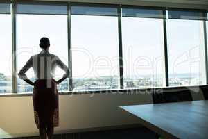 Female business executive looking through window in conference room