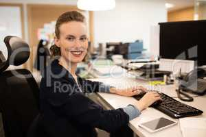 Portrait of businesswoman typing on keyboard at office