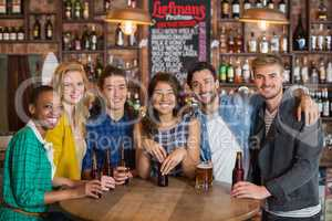 Portrait of young friends with beers by table in pub