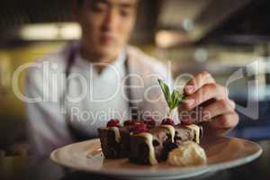 Male chef garnishing dessert plate