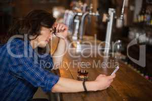 Depressed young man using mobile at pub