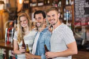 Happy friends holding beer bottles at pub