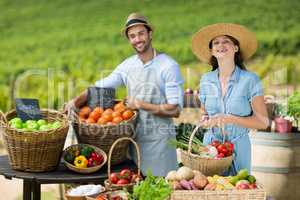 Smiling friends selling fruits and vegetables