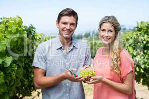 Portrait of happy couple holding grapes and pruning shears at vineyard