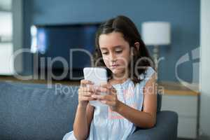Unhappy girl sitting on sofa and using mobile phone in living room
