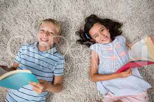 Portrait of siblings lying on rug and reading book in living room