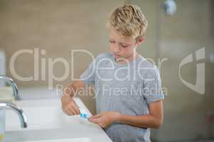 Boy putting toothpaste on brush in bathroom