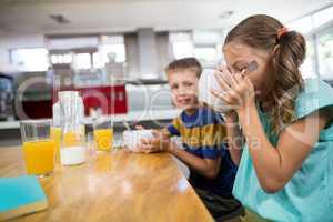Sibling having breakfast cereal in kitchen