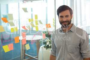 Portrait of confident businessman standing by strategy on glass at office