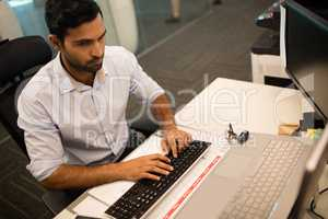Businessman typing on keyboard at office dsek