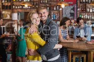 Smiling young couple hugging in pub