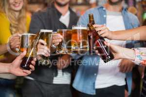 Friends toasting beer glasses and bottles in pub