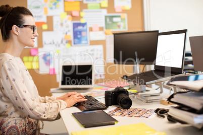 Smiling designer typing on computer keyboard