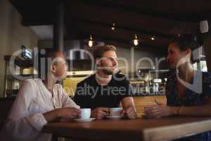 Friends interacting while having coffee