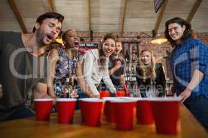 Young friends playing beer pong game in bar