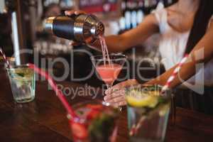 Mid section of female bartender pouring cocktail drink in the glass