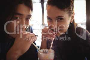 Portrait of couple having milkshake