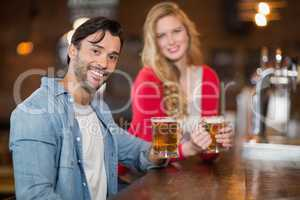 Young man and woman holding beer glasses at pub