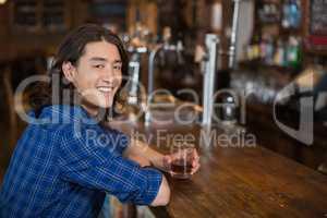 Young man using laptop at bar counter