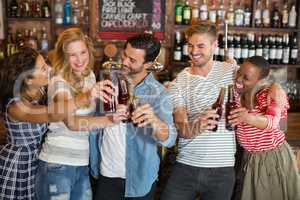 Group of friends toasting beer bottles at pub