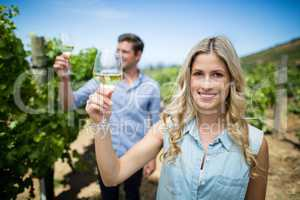 Smiling young woman holding wineglass at vineyard
