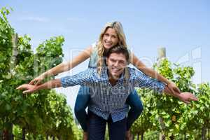 Portrait of happy young couple piggybacking at vineyard