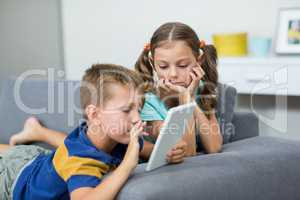Siblings using digital tablet in living room