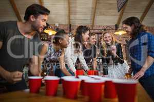 Happy friends playing beer pong game in bar