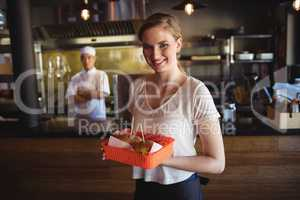 Waitress holding burger in tray
